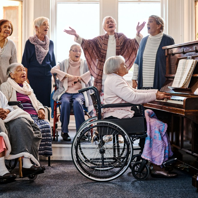 Group of senior residents singing around the piano