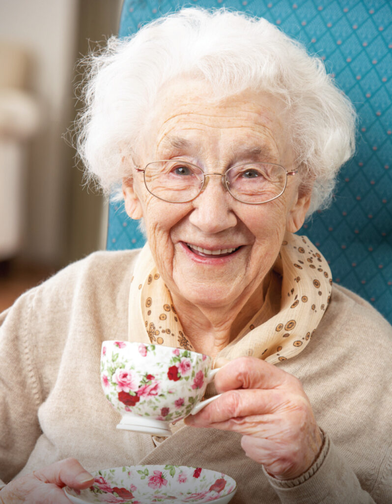 Happy senior woman sipping a warm cup of tea